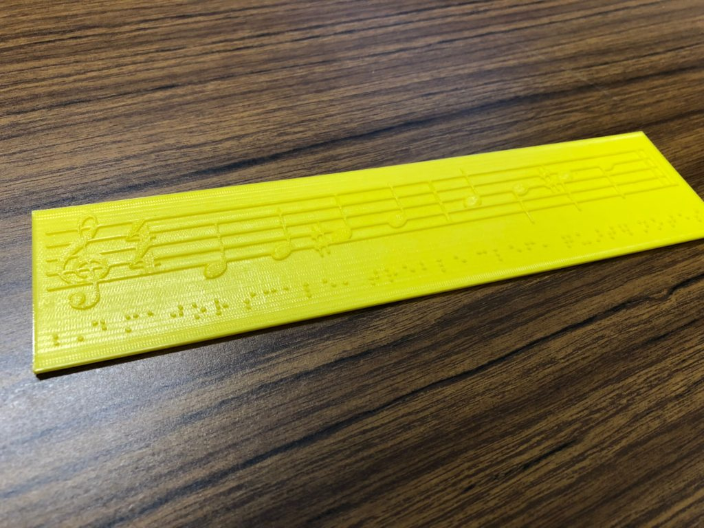 Photo of a D major scale in staff notation, embossed in plastic from a 3d printer.